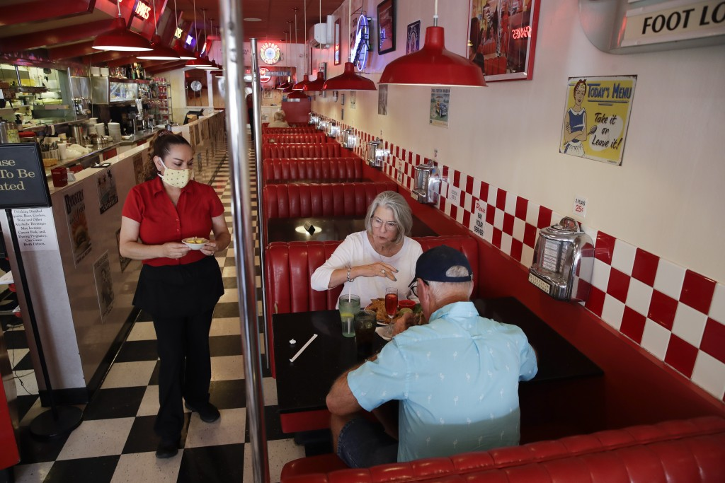 Lynn Tanner, center, and her husband Ryan, bottom right, are served lunch at Busy Bee Cafe Thursday, May 21, 2020, in Ventura, Calif. State public hea...