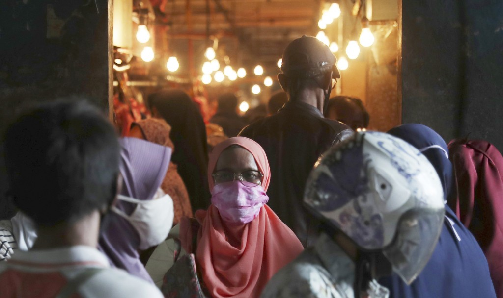 Muslim women wear face masks as they shop in preparation of the upcoming Eid al-Fitr holiday that marks the end of the holy fasting month of Ramadan a...