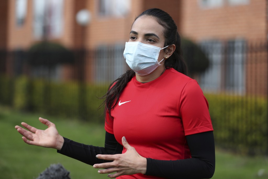 Wearing a face mask, Venezuelan soccer player María Alejandra Peraza, who played last season with Colombia's Millonarios women's team, speaks during a...