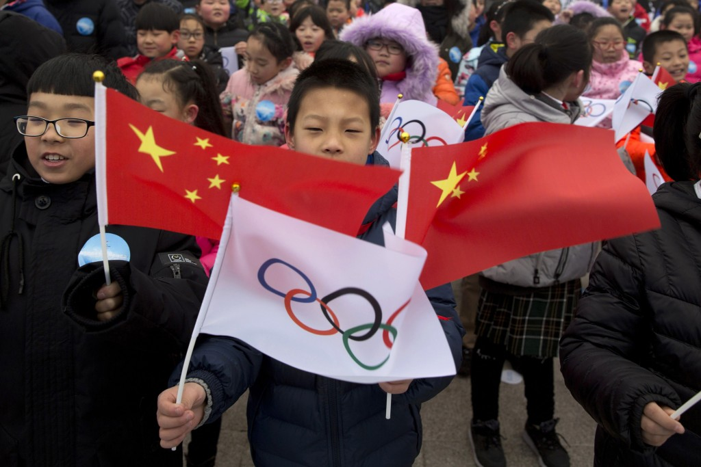 FILE - In this Feb. 27, 2018, file photo, a child waves a Chinese national flag and an Olympic flag during a ceremony to mark the arrival of the Olymp...