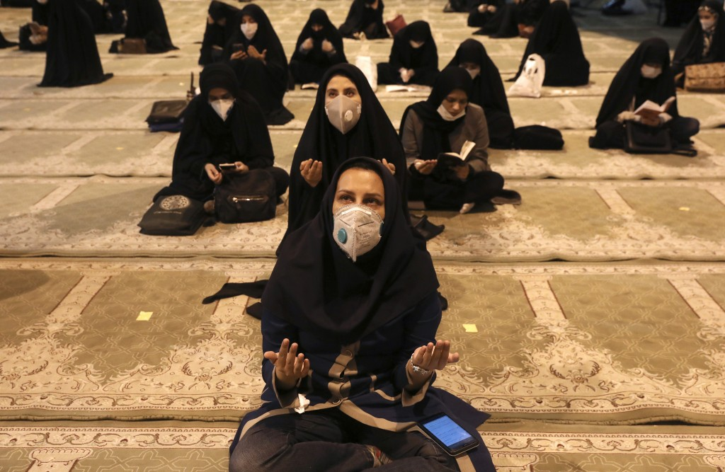 FILE - In this May 12, 2020, file photo, worshippers wearing protective face masks to help prevent the spread of the coronavirus pray at the mosque of...