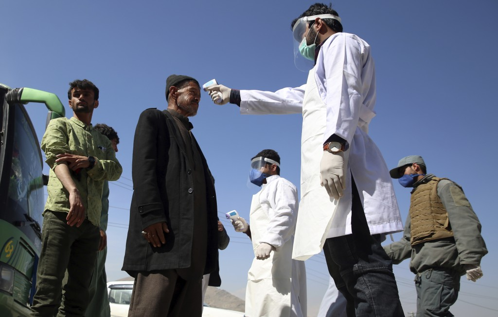 FILE - In this Sunday, March 22, 2020 file photo, health workers measure the temperature of Afghan passengers in an effort to prevent the spread of th...