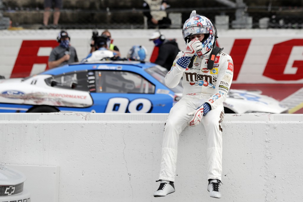 Kyle Busch sits on the wall as Chase Briscoe celebrates behind him after Briscoe edged out Busch to win the NASCAR Xfinity series auto race Thursday, ...