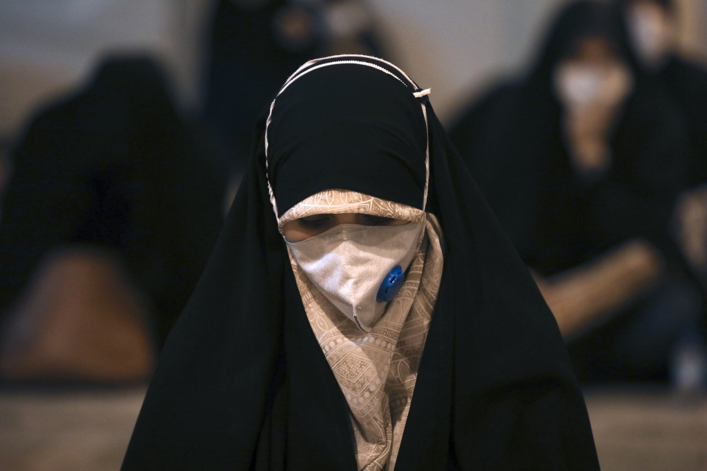 FILE - In this May 12, 2020, file photo, a worshipper wearing a protective face mask to help prevent the spread of the coronavirus prays at the mosque...