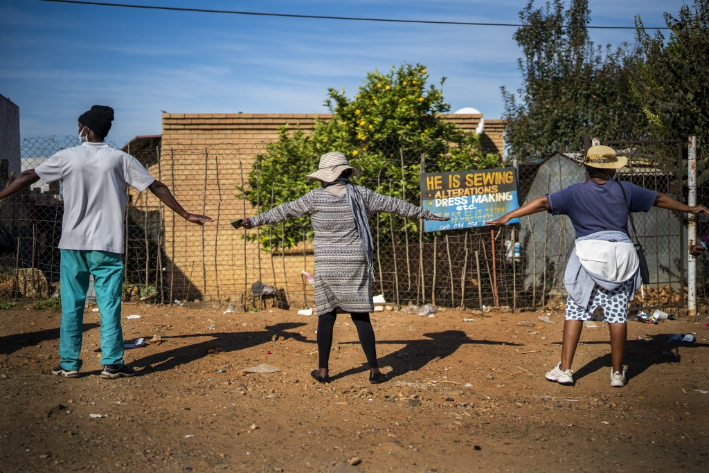 People practice safe distancing as they line up to receive food handouts in the Olievenhoutbos township of Midrand, South Africa, May 2, 2020. (AP Pho...