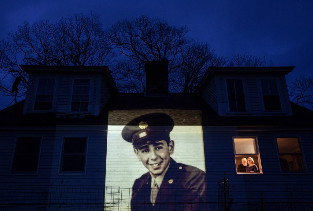 An image of veteran Emilio DiPalma, is projected onto the home of his daughter, Emily Aho, left, as she looks out a window with her husband, George, i...