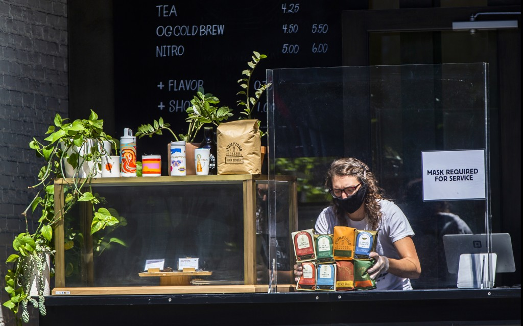 A barista sets bags of coffee behind a plexiglass barrier at a counter set outdoors of Stumptown Coffee Roasters downtown Los Angeles Thursday, May 21...