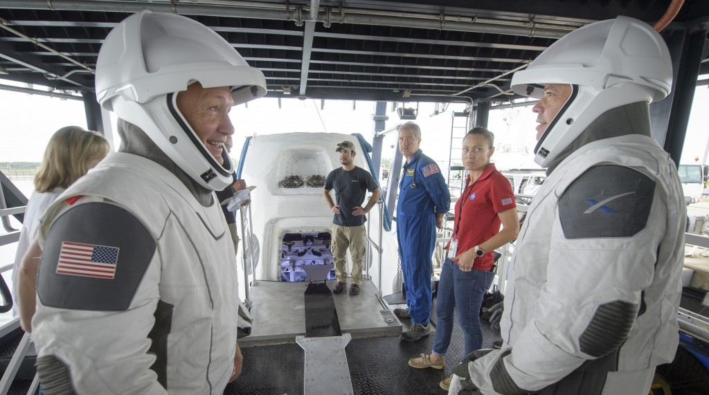 FILE - In this Aug. 13, 2019 file photo, NASA astronauts Doug Hurley, left, and Bob Behnken work with teams from NASA and SpaceX to rehearse crew extr...