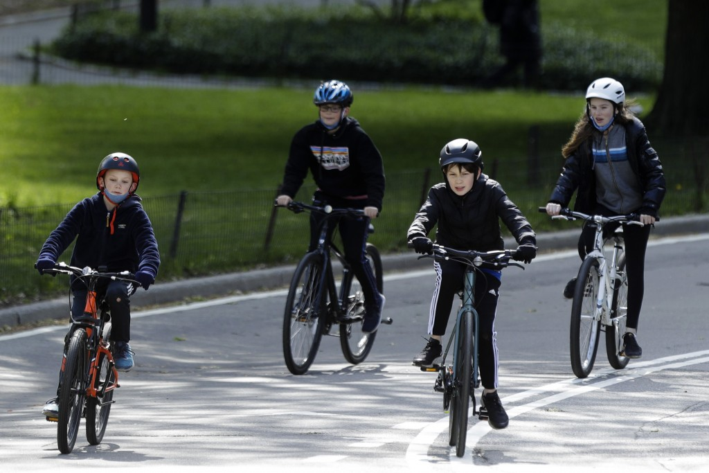 Youngsters ride bicycles through Central Park, Saturday, May 9, 2020, in New York. (AP Photo/Frank Franklin II)