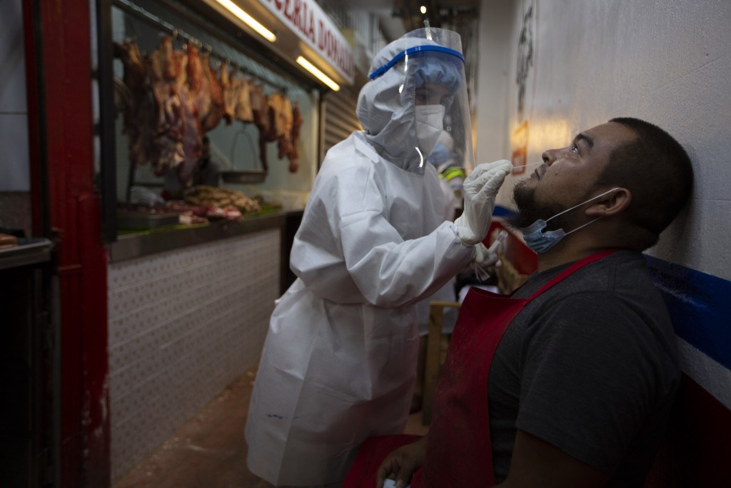 A medical worker from the Ministry of Health wearing a protective suit takes a sample to test for COVID-19 from a butcher at La Terminal market in Gua...