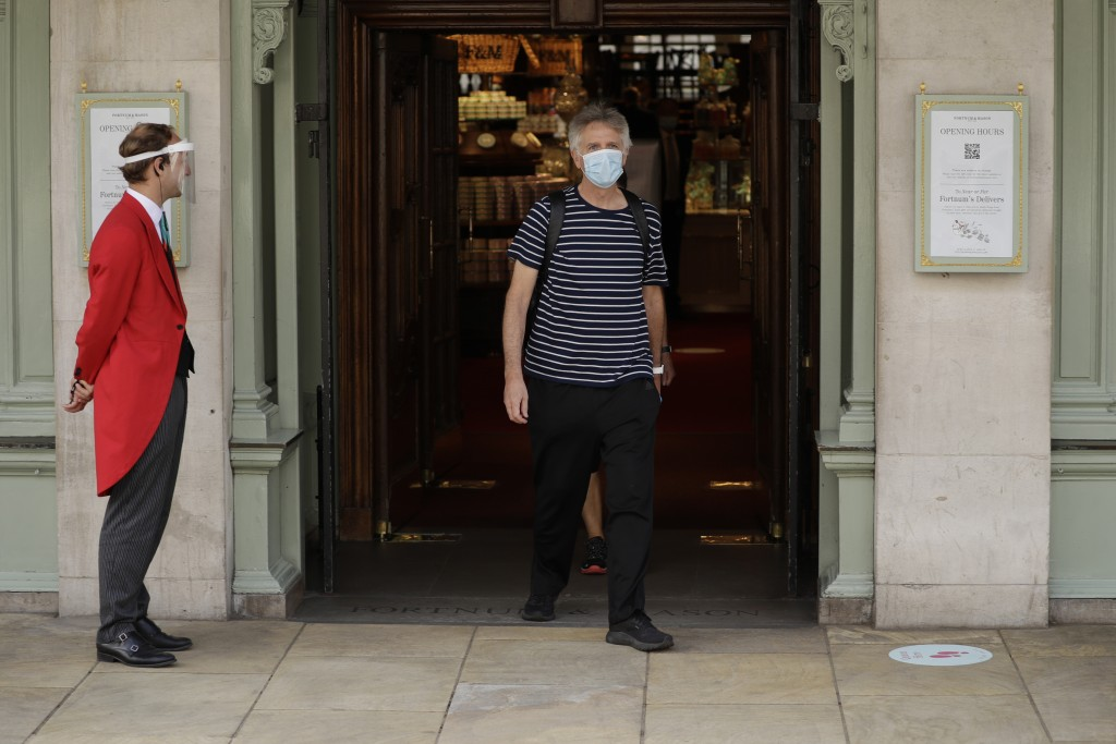 A doorman wearing a face shield and mask to protect from coronavirus stands outside the main entrance of the Fortnum & Mason department store as a cus...