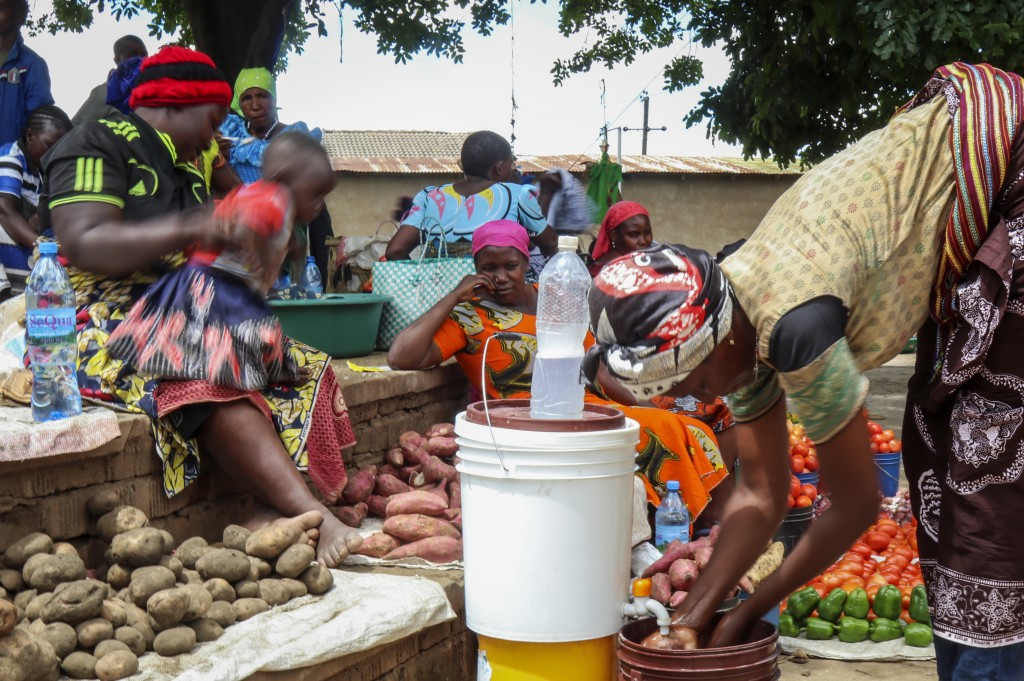 In this photo taken Monday, March 30, 2020, traders sit by the vegetables they are selling at a street market in Dodoma, Tanzania. The country's numbe...