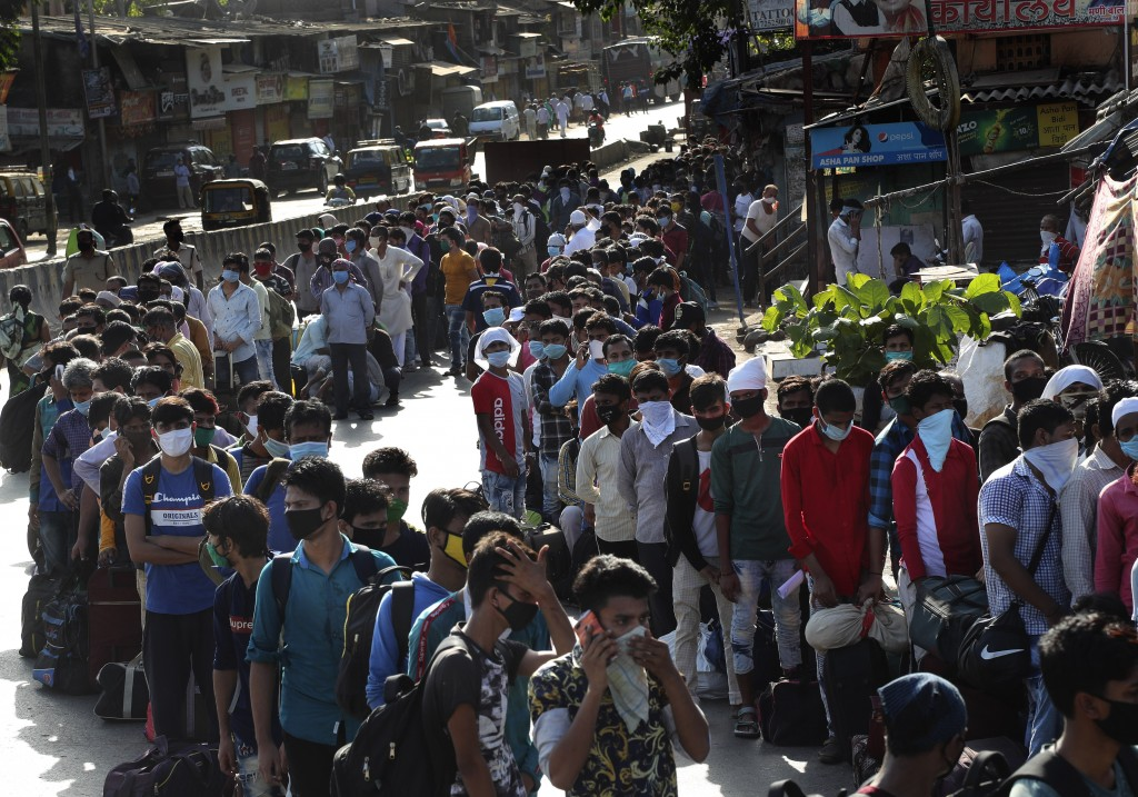 Migrant workers line up to board buses for their onward journey by train to their home states, at Dharavi, one of Asia's largest slums, in Mumbai, Ind...