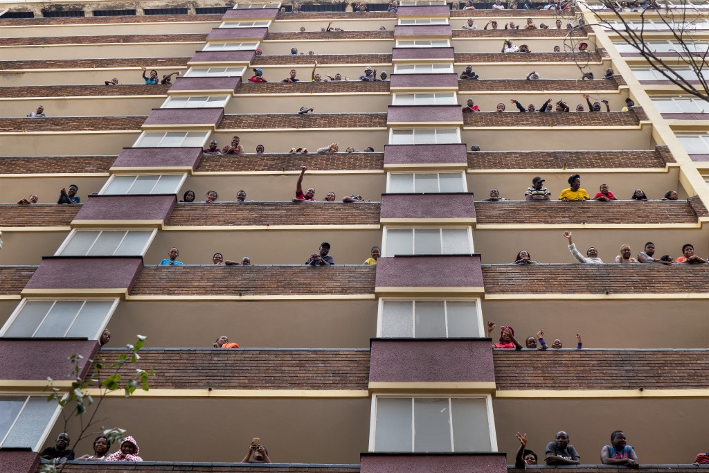 Residents of the densely populated Hillbrow neighborhood stand and wave from their balconies during the coronavirus outbreak in Johannesburg during Ma...
