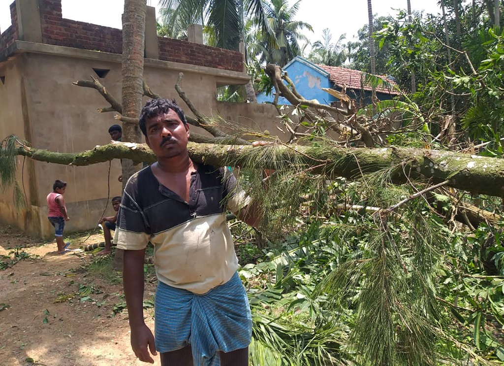 A villager clears tree branches fallen in front of his house after Cyclone Amphan hit the region, at Baguranjalpai village in East Midnapore district ...