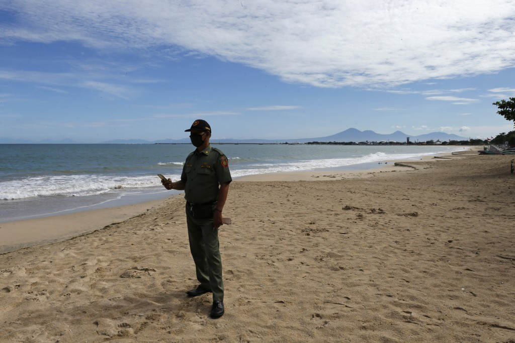 A security guard wearing a protective mask to help curb the spread of the coronavirus as he guards an empty beach in Bali, Indonesia on Friday, May 22...