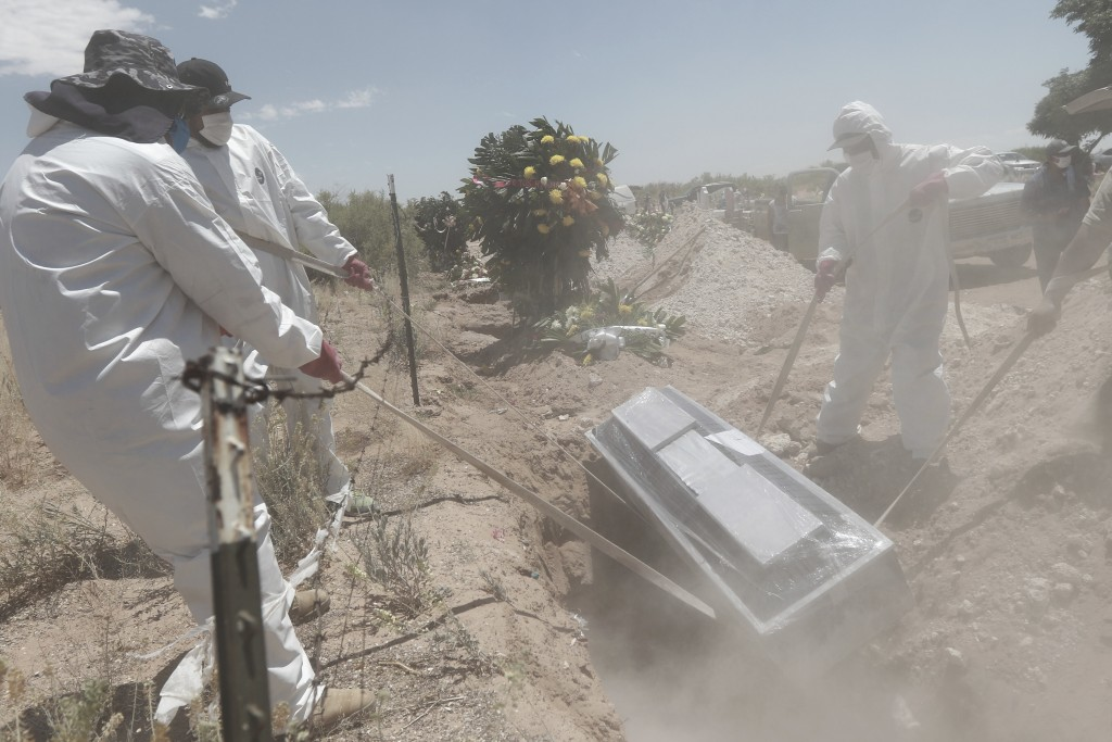 Workers in full protection gear against the spread of the new coronavirus bury a coffin in an area of the San Rafael municipal cemetery set apart for ...