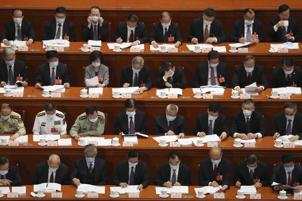 Delegates read a government work report during the opening session of China's National People's Congress (NPC) at the Great Hall of the People in Beij...