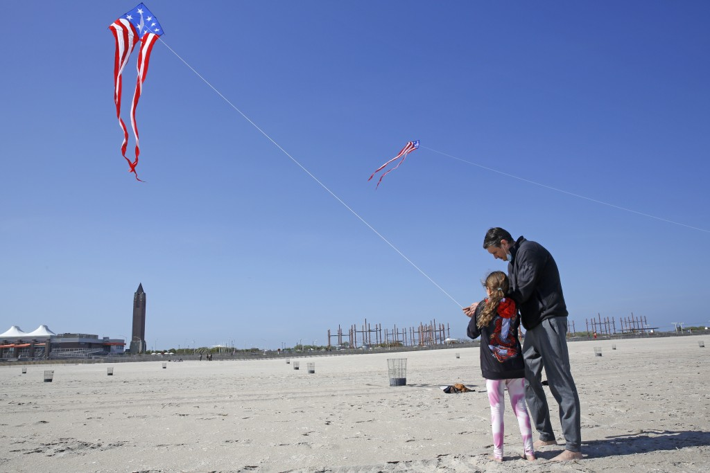 Kaylee Wilmer, 9, of Lindenhurst, N.Y., gets help from her father, Stephen Wilmer, as they fly a kite, Thursday, May 21, 2020, at Jones Beach in Wanta...