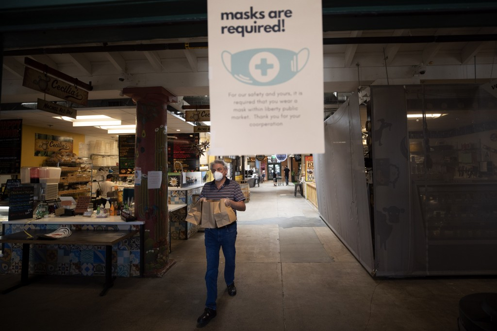 A man passes under a sign as he carries a takeout order from Liberty Public Market Thursday, May 21, 2020, in San Diego. San Diego County began to rel...