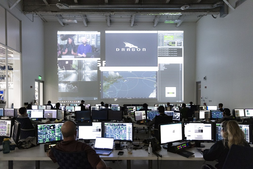 In this Thursday, March 19, 2020 photo made available by SpaceX, SpaceX teams in Firing Room 4 at NASA's Kennedy Space Center in Cape Canaveral, Fla.,...