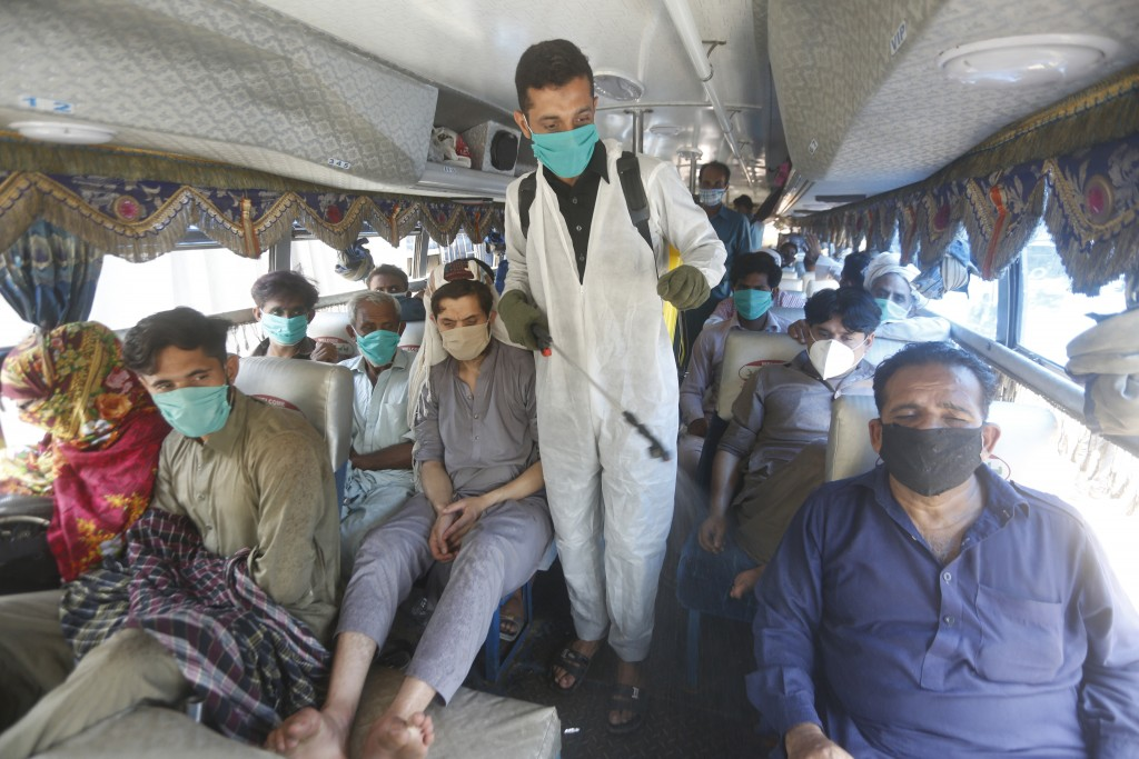 A volunteer sprays disinfectant on passengers traveling to their villages to celebrate the upcoming Eid al-Fitr holiday that marks the end of the Musl...