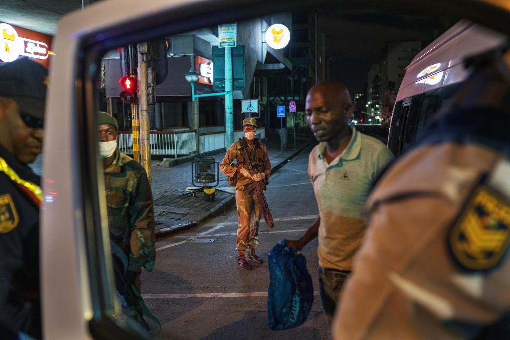 South African Defense Forces and police check a minibus driver who violated the lockdown in Johannesburg, South Africa, March 27, 2020. Police and arm...