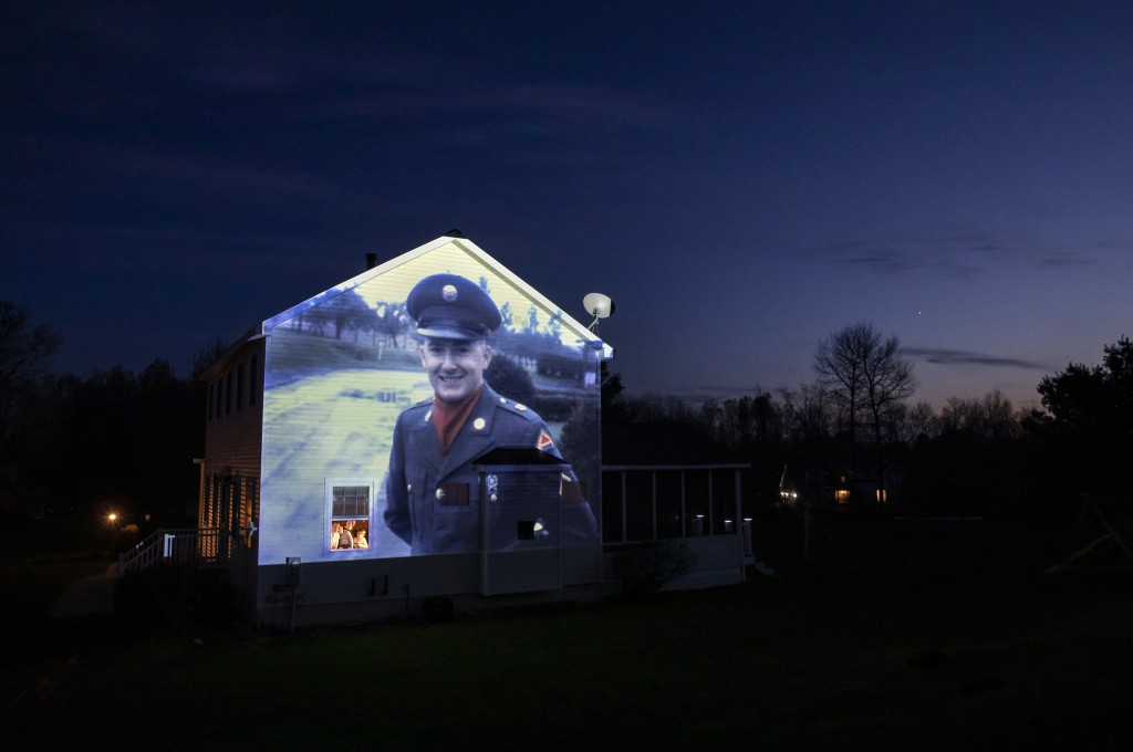 An image of veteran Chester LaPlante is projected onto the home of his son, Randy LaPlante, as he looks out a window with his wife, Nicole, and their ...