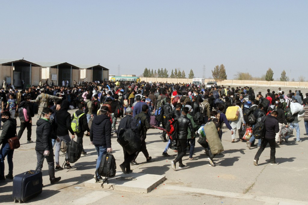 FILE - In this March 18, 2020, file photo, thousands of Afghan refugees walk as they enter Afghanistan at the Islam Qala border crossing with Iran, in...