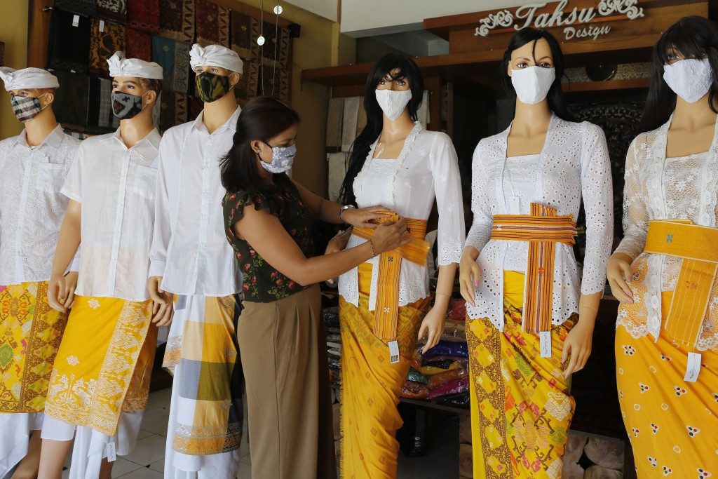 A woman wearing a protective mask prepares to open her traditional Balinese cloth shop in Bali, Indonesia on Friday, May 22, 2020. (AP Photo/Firdia Li...
