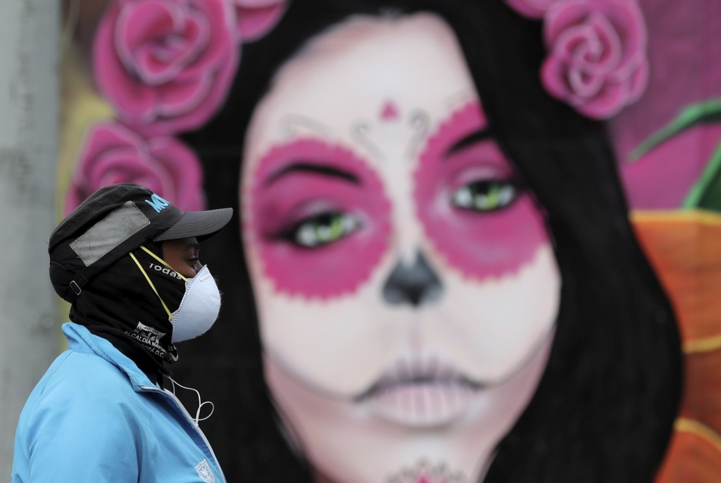 A woman wearing a face mask amid the spread of the new coronavirus walks past a Catrina mural in Bogota, Colombia, Thursday, May 21, 2020. (AP Photo/F...