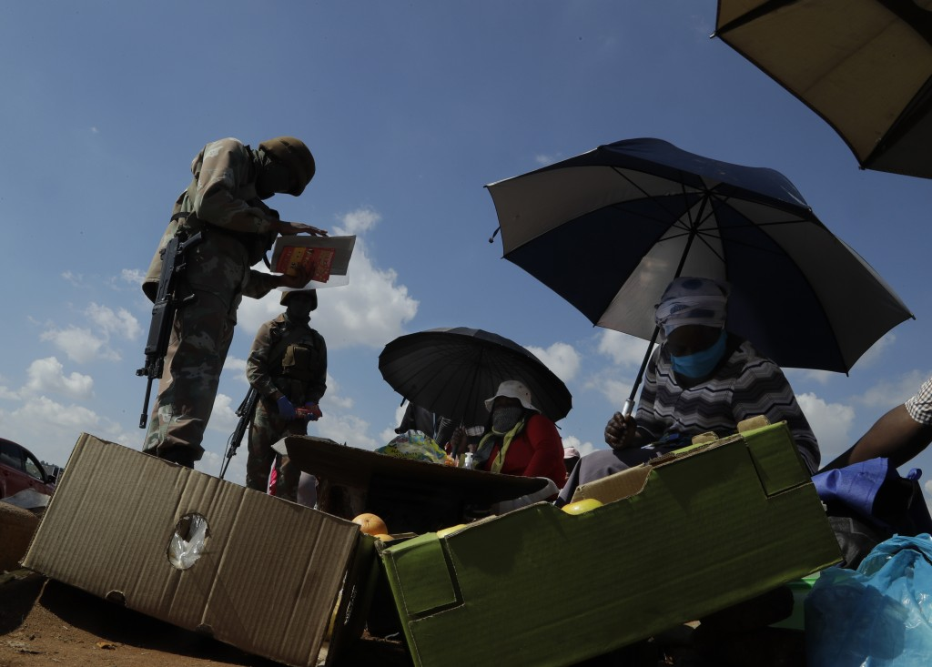 Soldiers check the permits of informal traders while on patrol in Soweto, South Africa, April 23, 2020, as the country remains in lockdown for a fourt...