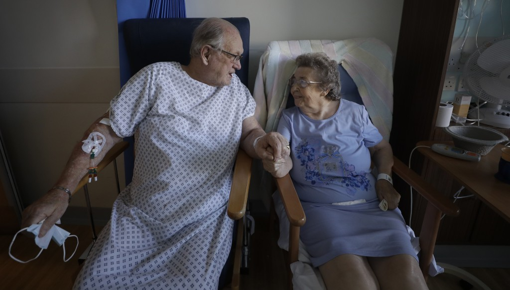 Coronavirus patients George Gilbert, 85 and his wife Domneva Gilbert 84, hold hands during a short visit, they are being treated in different areas, a...