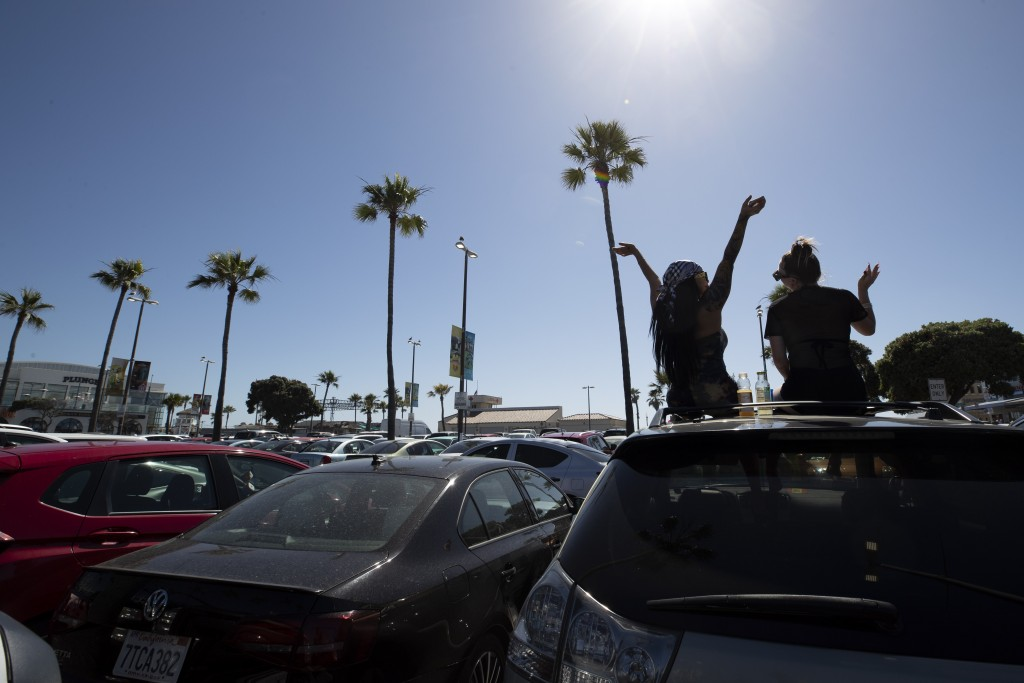 Two women listen to music as they sit through their sunroof in a beach parking lot Thursday, May 21, 2020, in San Diego. San Diego County began to rel...