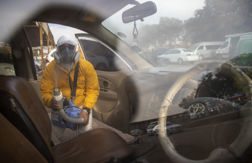 A man wearing personnel protection equipment, disinfects a taxi during a procedure to help prevent the spread of the coronavirus at Tembisa township i...