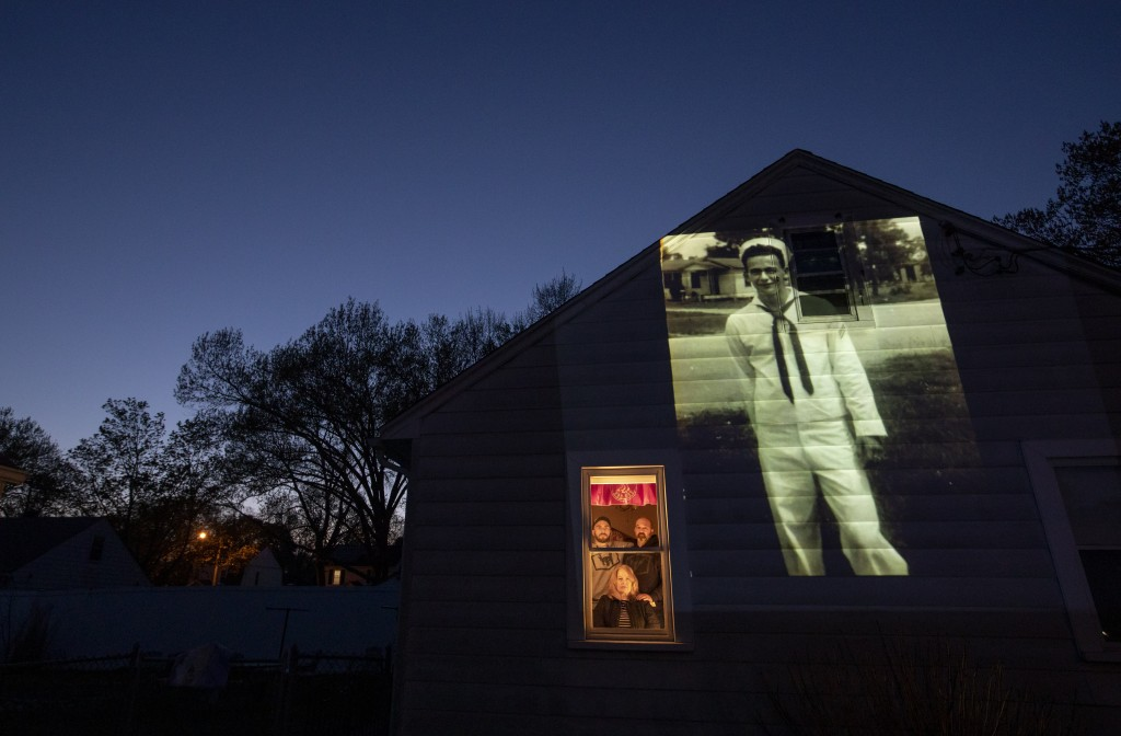 An image of veteran James Mandeville is projected onto the home of his daughter, Laurie Mandeville Beaudette, as she looks out a window with her son, ...