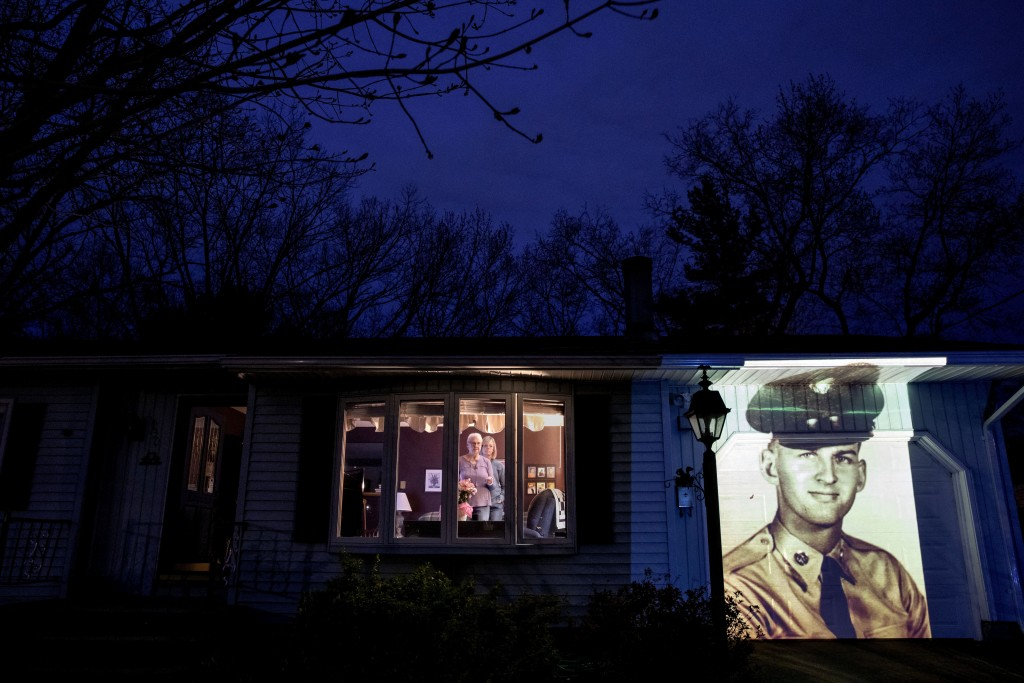 An image of veteran Francis Foley is projected onto the home of his wife, Dale Foley, left, as she looks out a window with their daughter, Keri Ruther...