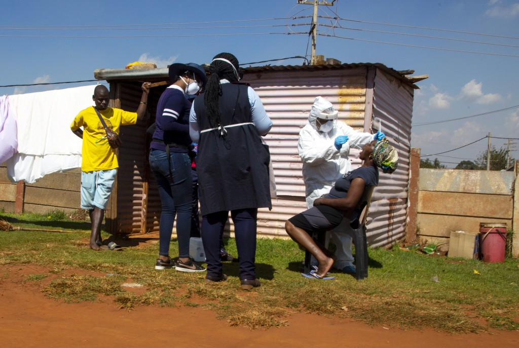 Health workers collect a sample for coronavirus testing, outside a shack during the screening and testing campaign aimed to combat the spread of COVID...