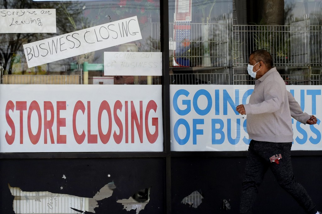 A man looks at signs of a closed store due to COVID-19 in Niles, Ill., Thursday, May 21, 2020. More than 2.4 million people applied for U.S. unemploym...