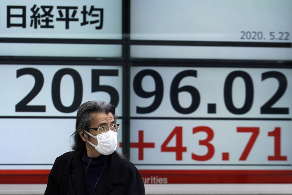 A man walks past an electronic stock board showing Japan's Nikkei 225 index at a securities firm in Tokyo Friday, May 22, 2020. Shares are slipping in...