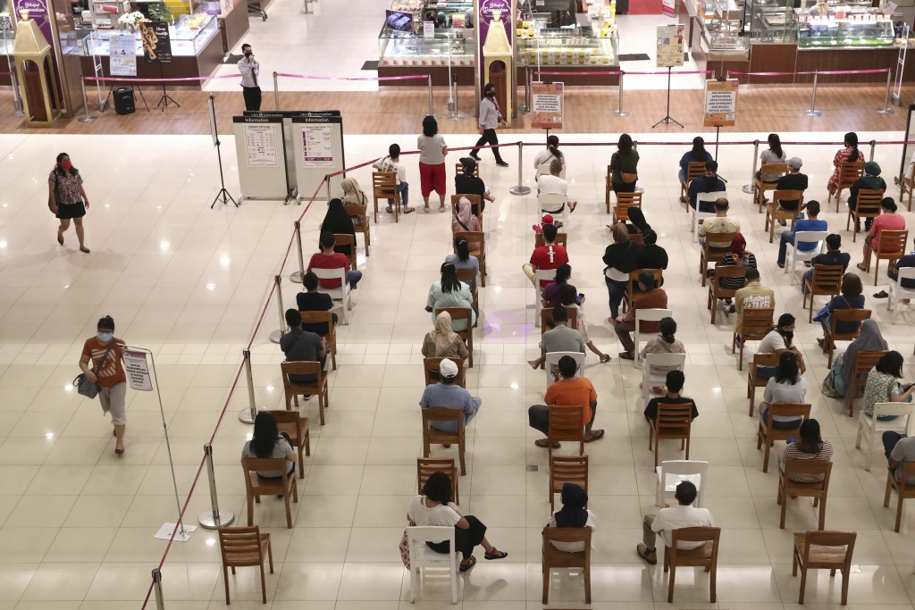 People sit spaced apart as a precaution against the new coronavirus outbreak while waiting for their turn to be allowed into a supermarket to shop, at...