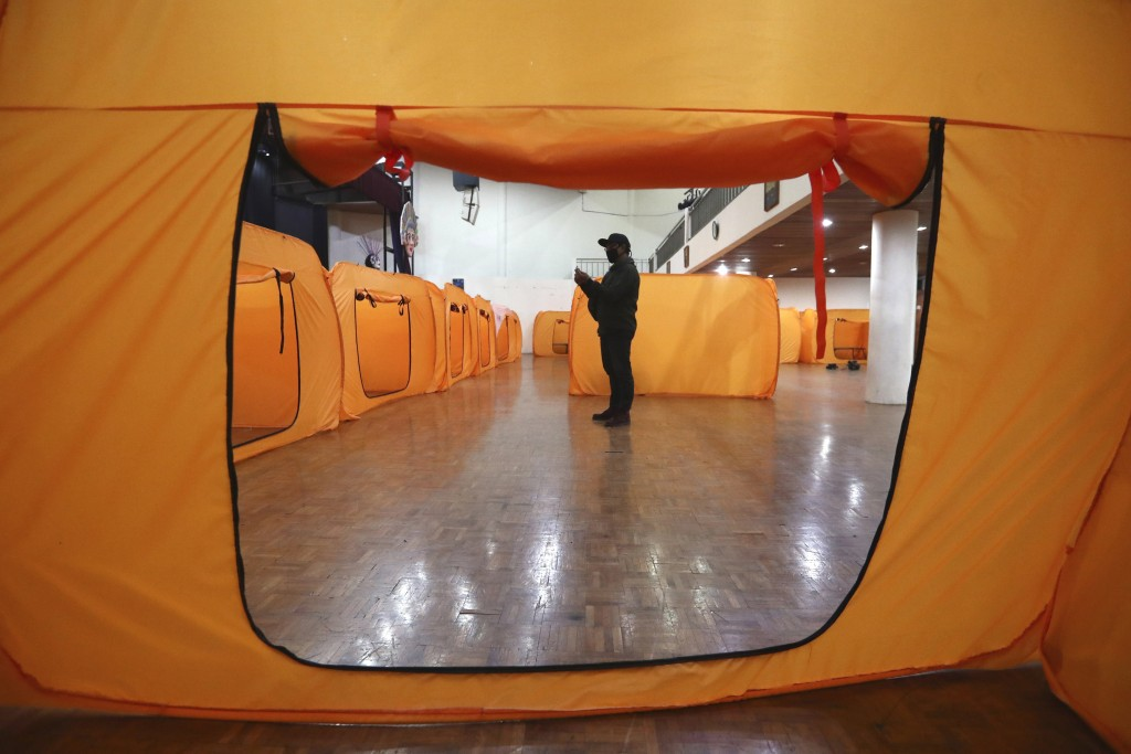 A government official inspect isolation tents that will serve as a quarantine facility for people showing symptoms of the COVID-19 at an indoor stadiu...