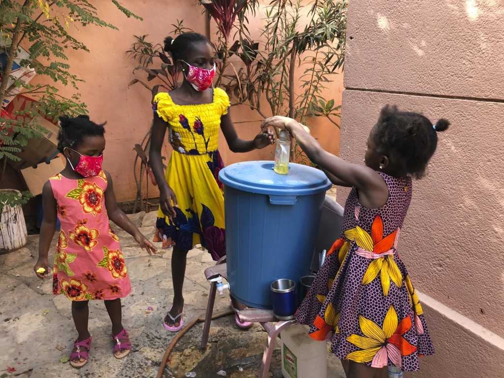In this May 21, 2020, photo, the Larson sisters wash their hands inside the gate at their home in Dakar, Senegal. The girls were adopted from Sierra L...