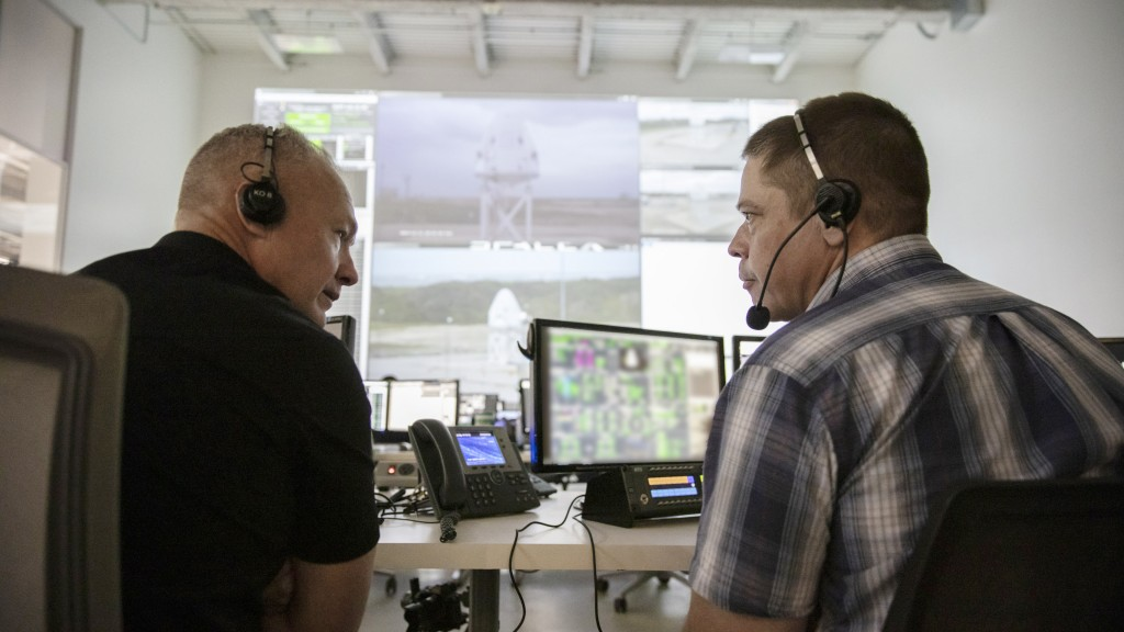 In this Nov. 13, 2019 photo made available by SpaceX, NASA astronauts Doug Hurley, left, and Bob Behnken, seated at consoles inside SpaceX Mission Con...