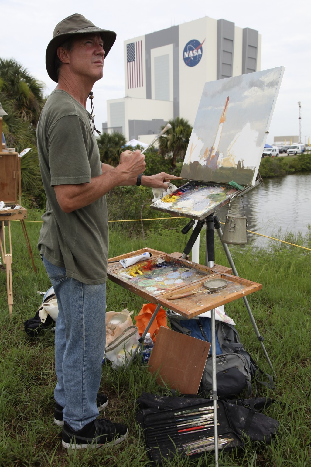 FILE - In this Friday, July 8, 2011 file photo, artist Larry Moore paints the scene at the Kennedy Space Center in Cape Canaveral, Fla., during the la...