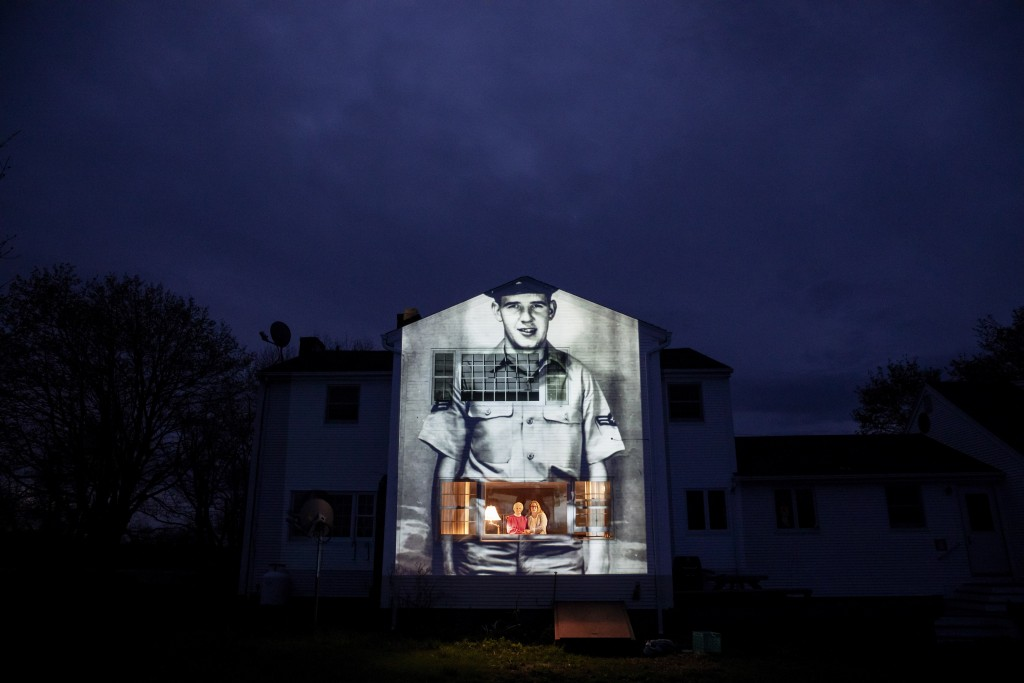 An image of veteran Charles Lowell is projected onto the home he shared with his wife, Alice, for 30 years as she stands at left with her daughter, Su...