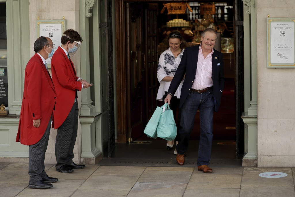 A doorman wearing a face shield and mask to protect from coronavirus stands outside the main entrance of the Fortnum & Mason department store as custo...