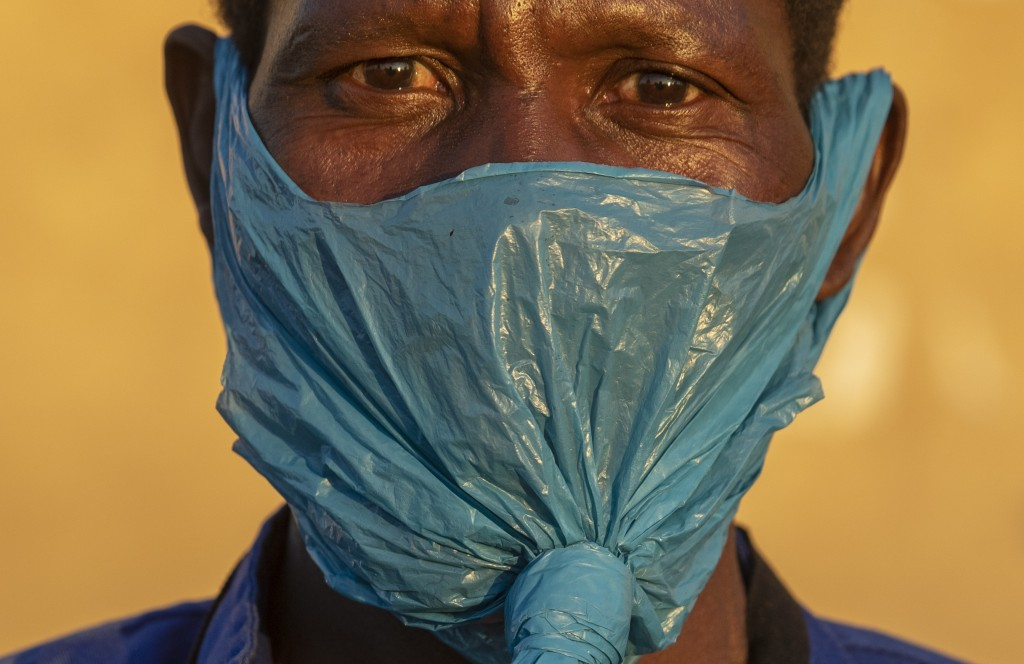 A man wears a plastic bag on his face as a precaution against the spread of the coronavirus, on the street in Katlehong, east of Johannesburg, South A...
