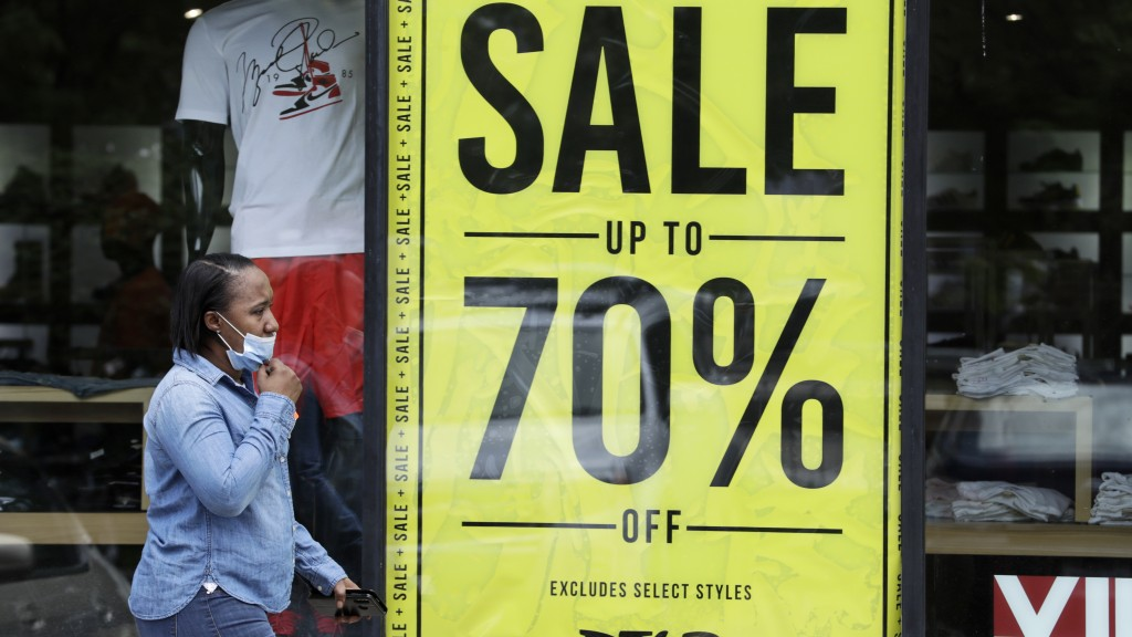 A woman walks past a store advertising sales at 70 percent off, Thursday, May 21, 2020, in Cleveland. More than 2.4 million people applied for U.S. un...