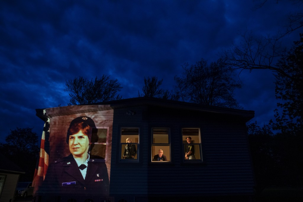 """An image of veteran Constance """"Kandy"""" Pinard is projected onto the home she grew up in with her sister, Tammy Petrowicz, left, and brothers, Paul, cen..."""